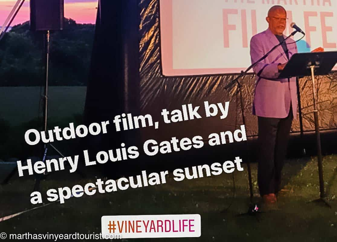 an outdoor film screen with a talk by Henry Louis GatesJr.