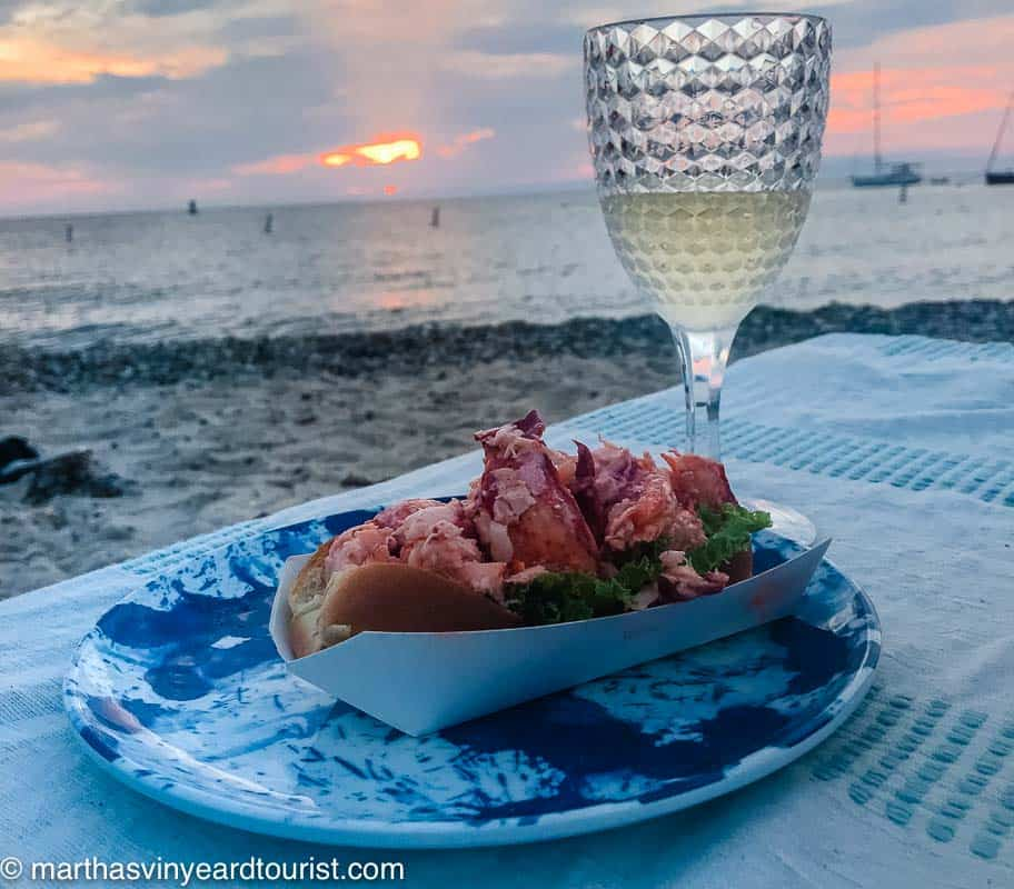 lobster roll on a plate and a glass of white wine