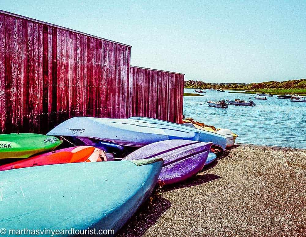 multicoloured kayaks lined up at chilmark pond
