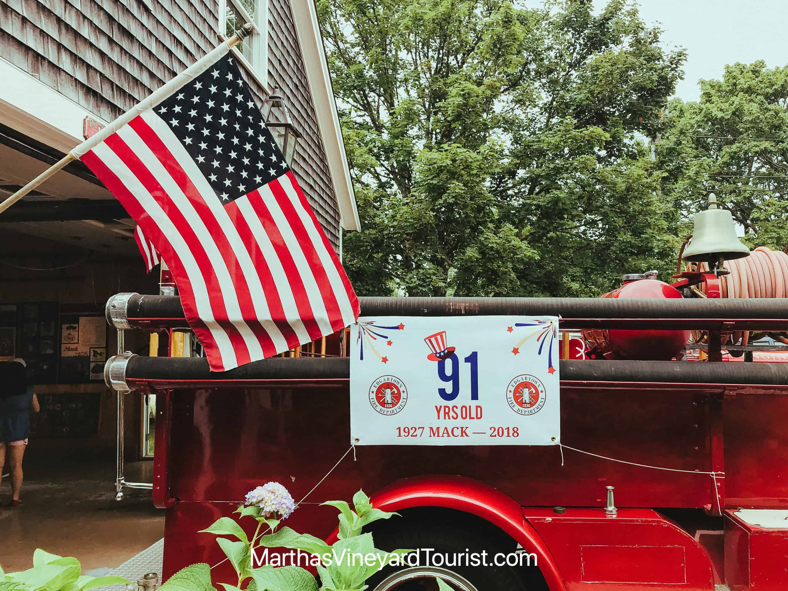 a vintage fire truck and an American flag in front of a grey shingle house