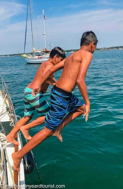 Two boys jumping off a boat into the ocean