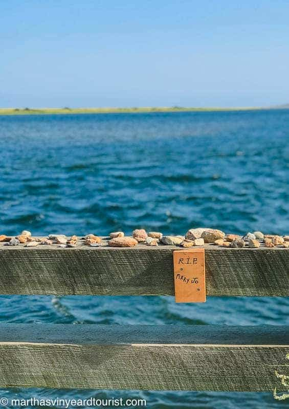 stones lain on a wooden bridge rail in tribute to Mary Jo Kopechne who died in 1969
