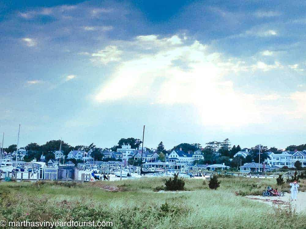 view of houses in Edgartown downtown from Lighthouse Beach with sun breaking through clouds