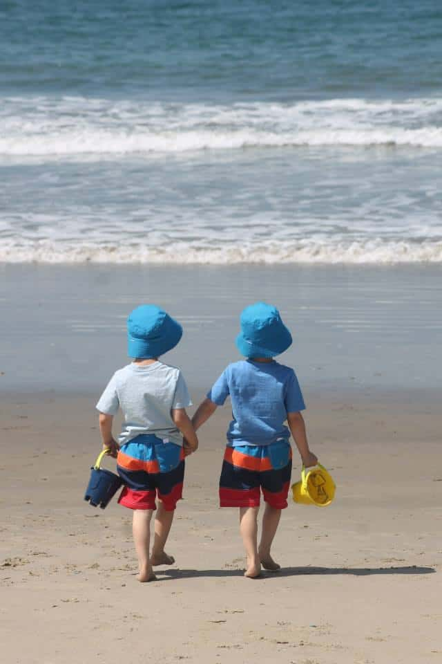 two kids at a beach with buckets