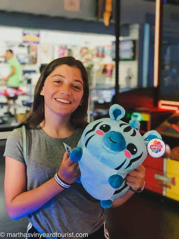 Girl with stuffed animal prize at an arcade