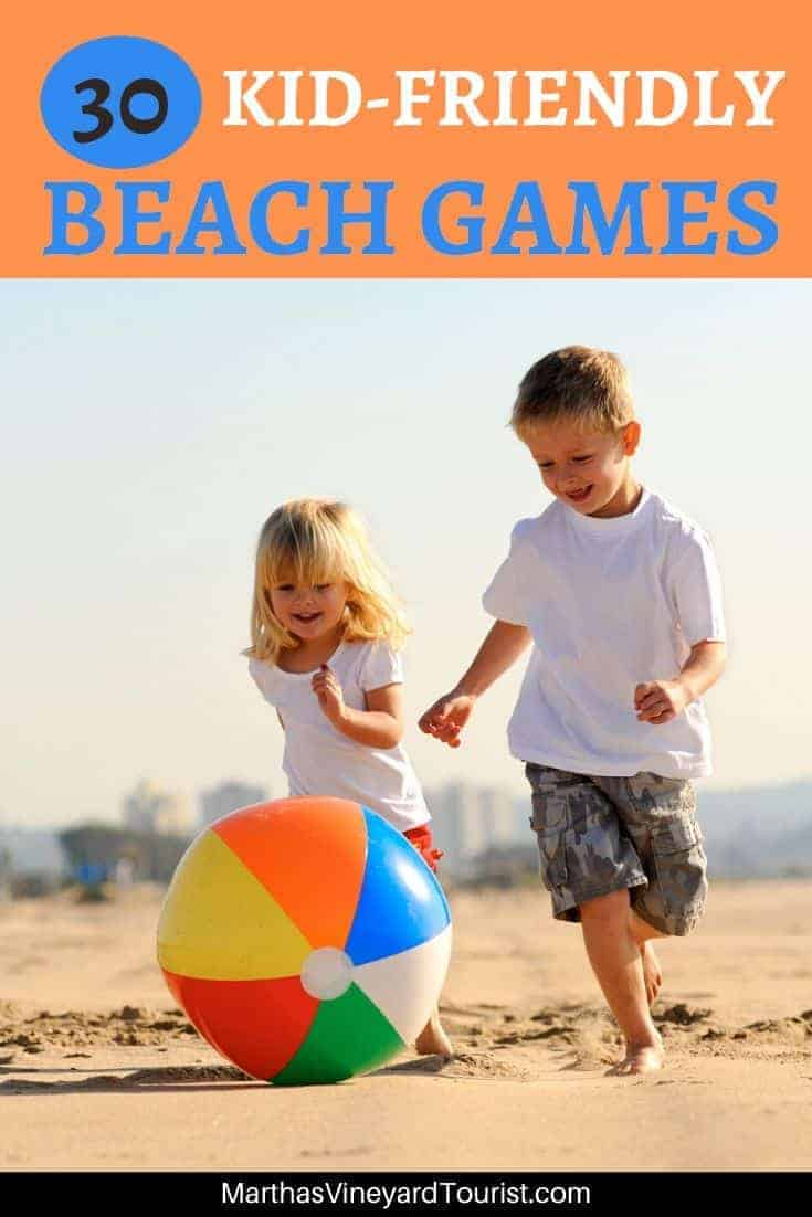 Two kids chasing a ball on the beach
