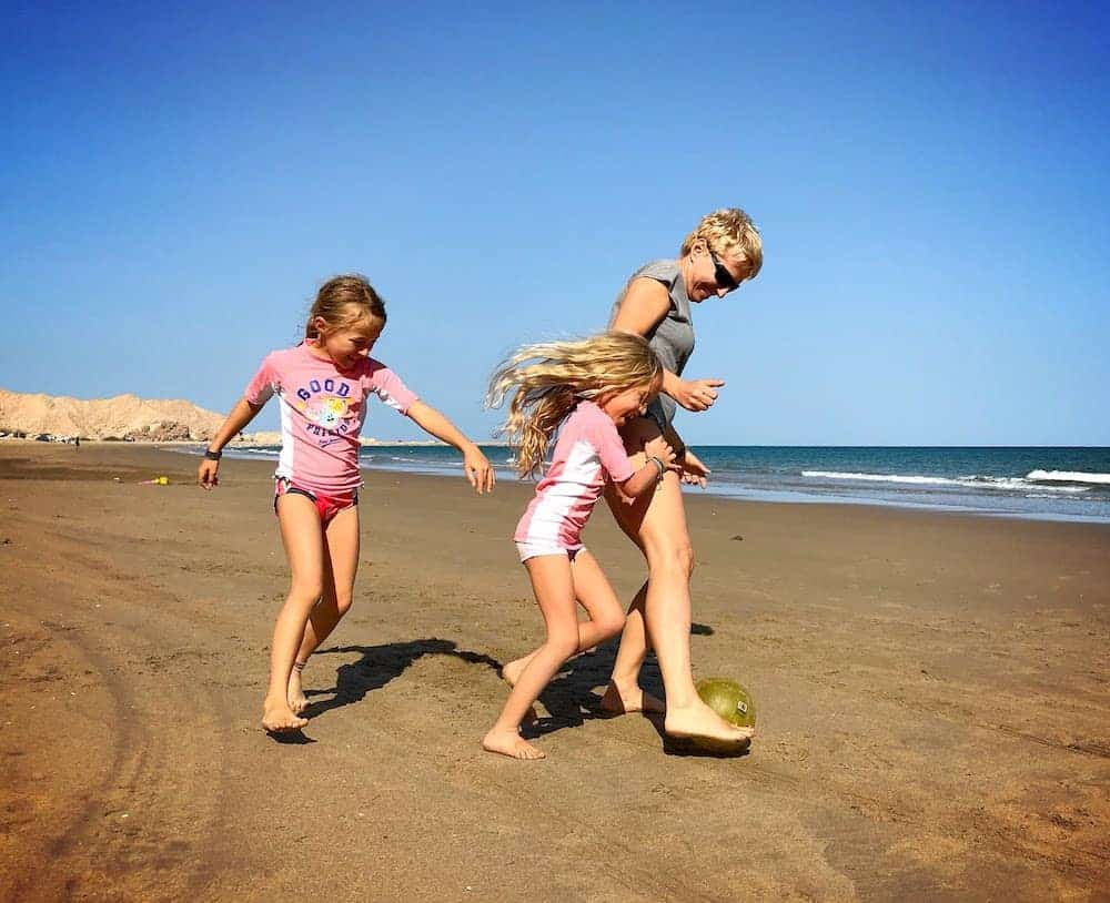 mom and two kids kicking a ball around on the beach