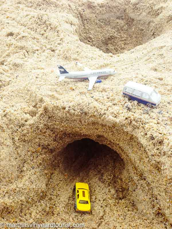 bridge and tunnel with toy cars and plane in sand