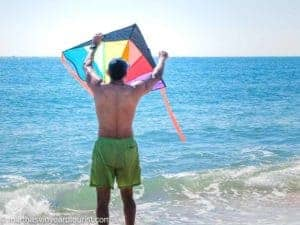 man flying a kite at the beach