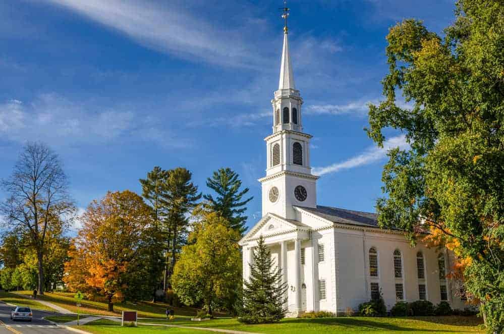 Traditional American Whithe Church with high Steeple under an Autumnal Blue Sk. Williamstown, MA.