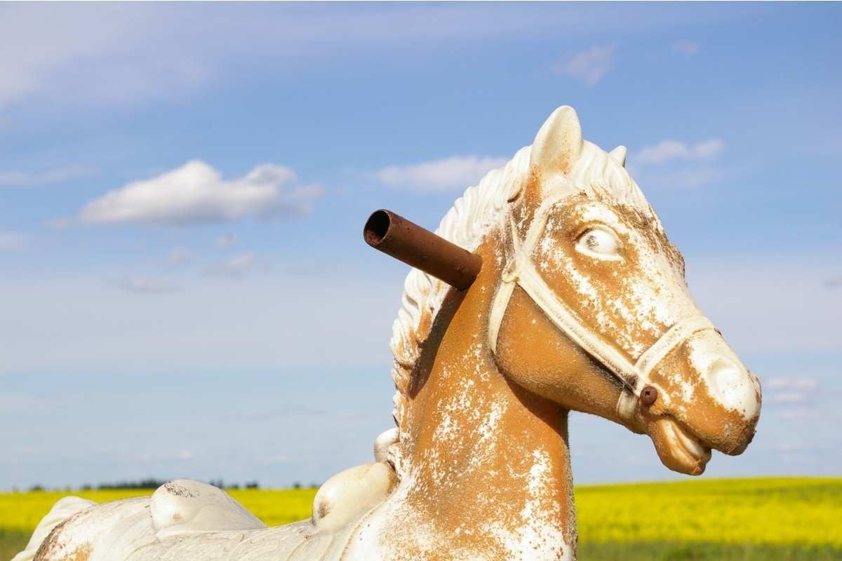 distressed wooden rocking horse in a field of yellow flowers