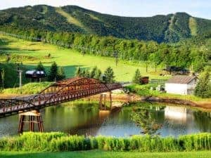 Vermont Green Mountains with a red metal bridge crossing the river and a white building