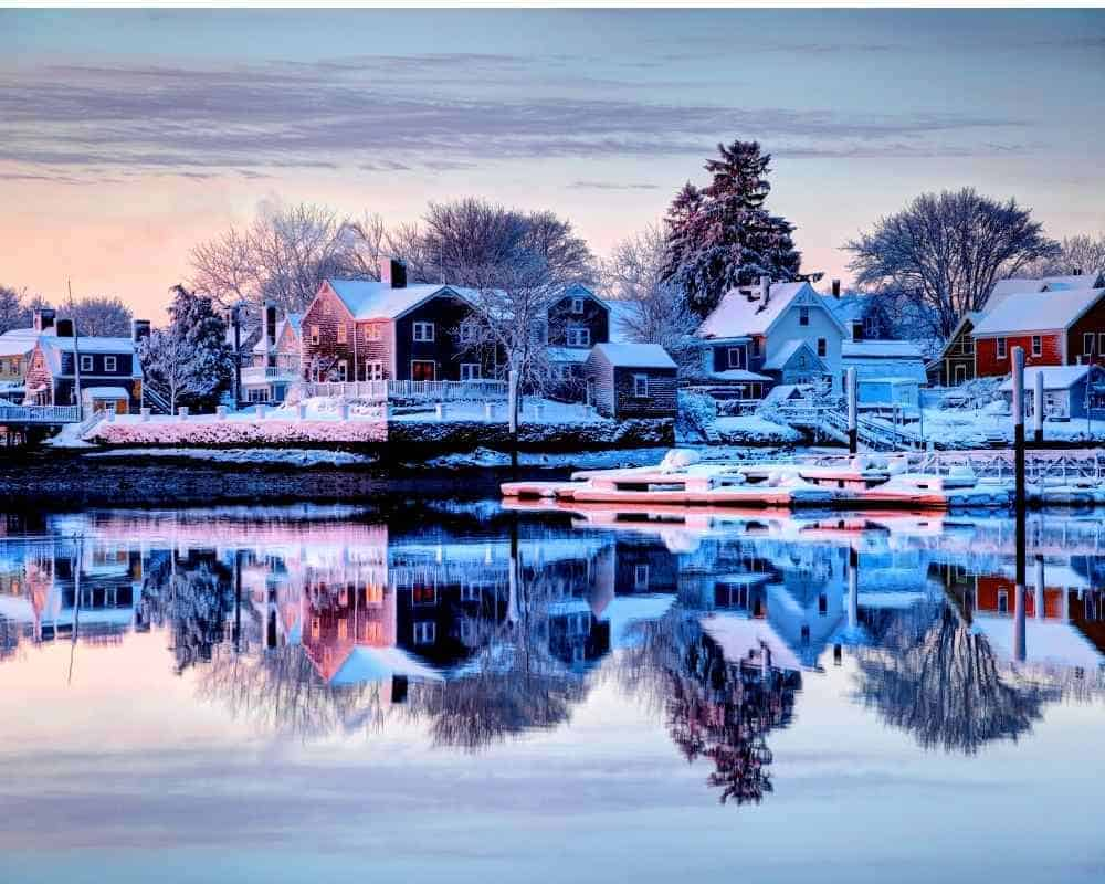 lake reflection of Portsmouth NH in winter with snow covered houses and trees