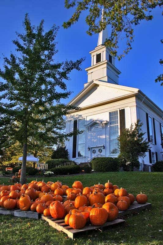 A white spired church on a blue sky day in Chatham with pumpkins on the lawn