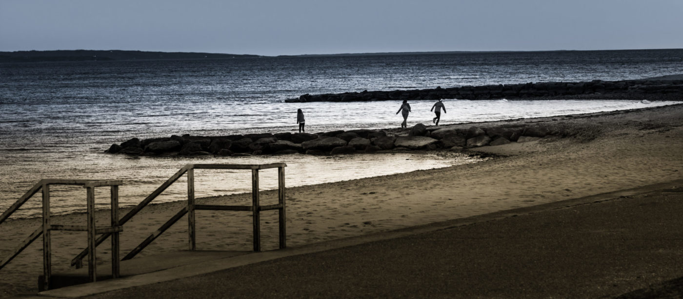 late afternoon on Falmouth Beach, Cape Cod, three chilrden playing in the distance